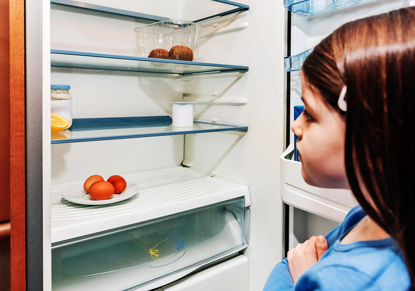 Young girl looks into an empty fridge