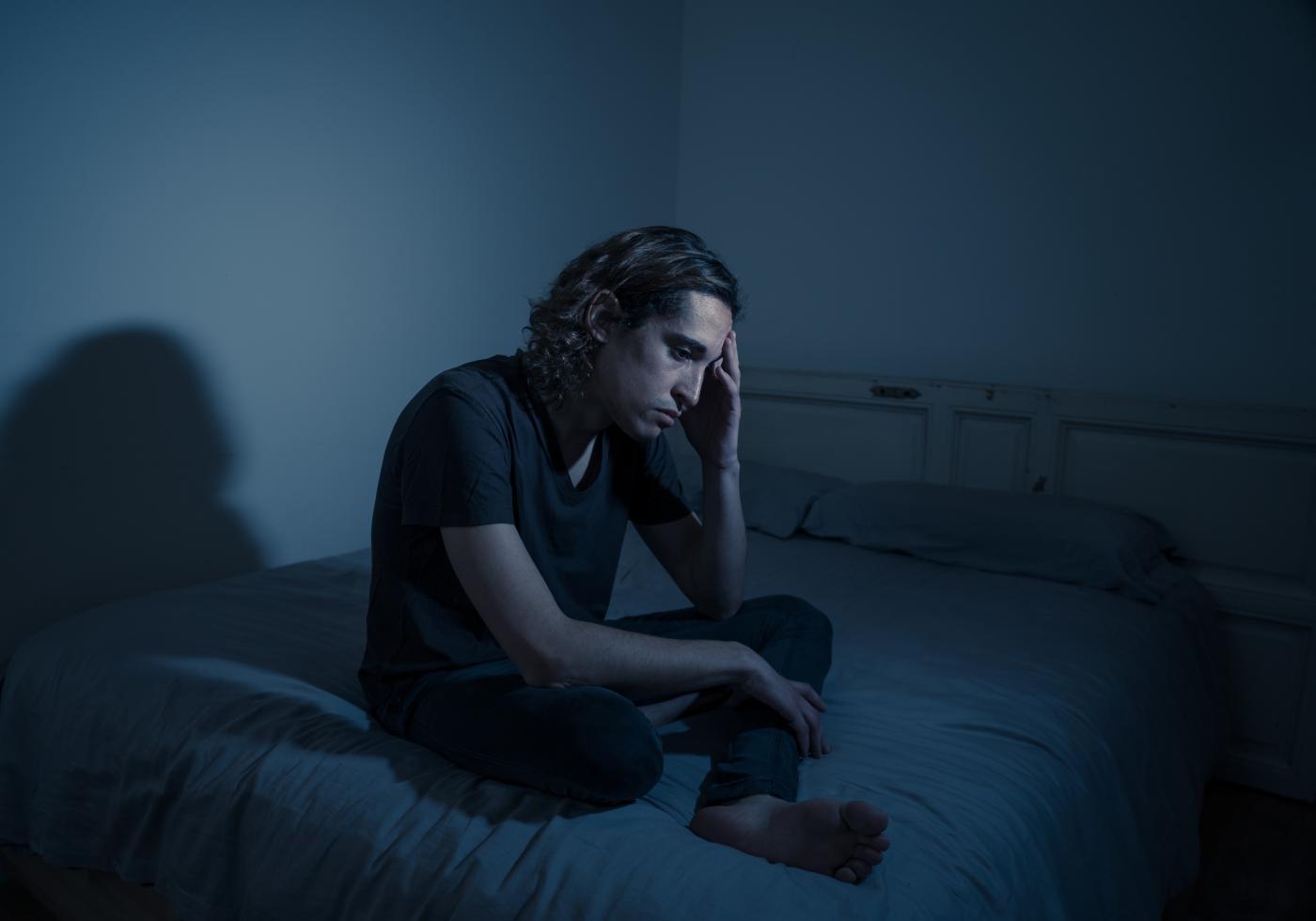 Depressed man sitting on his bed