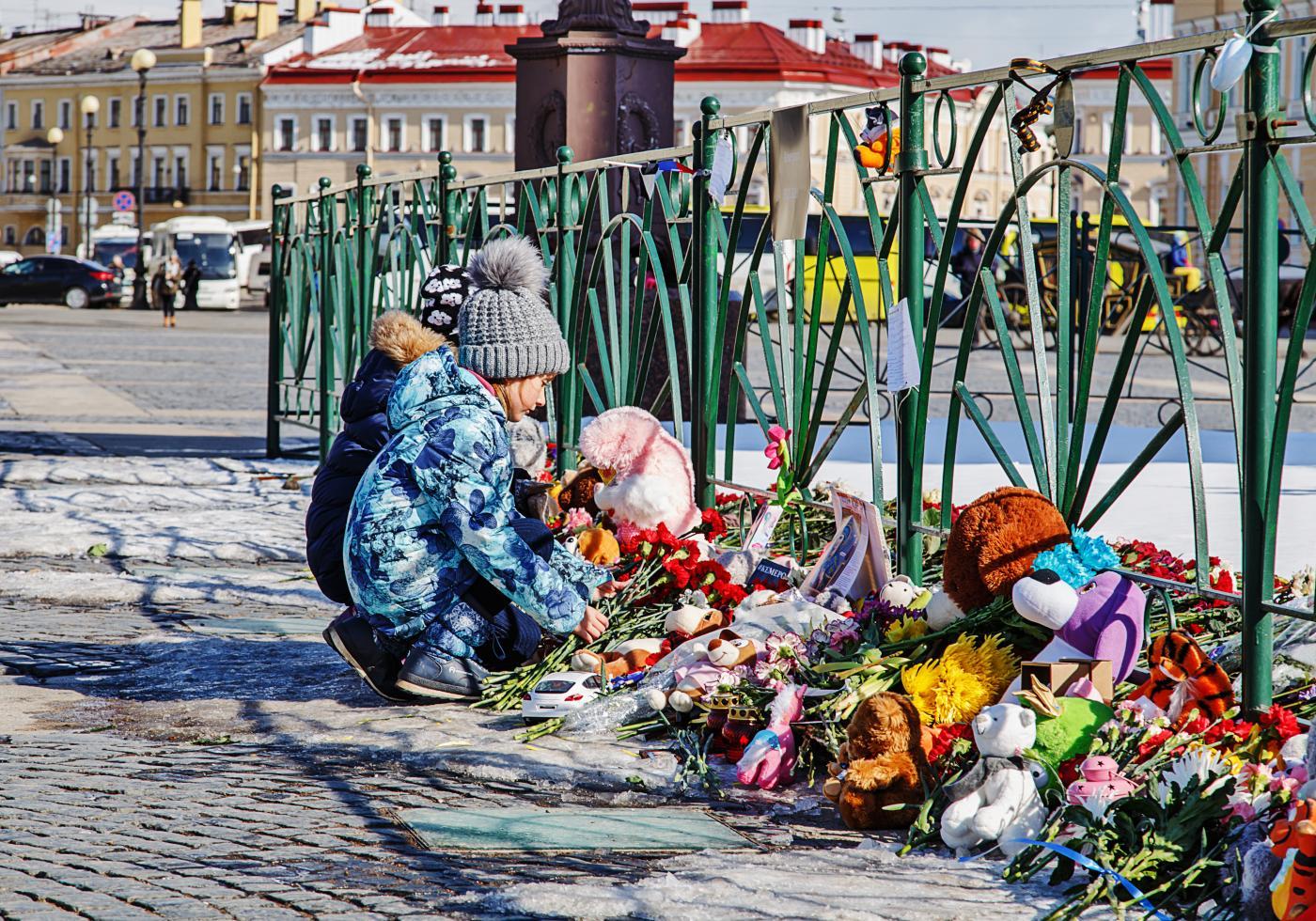 Child lays memorial flowers