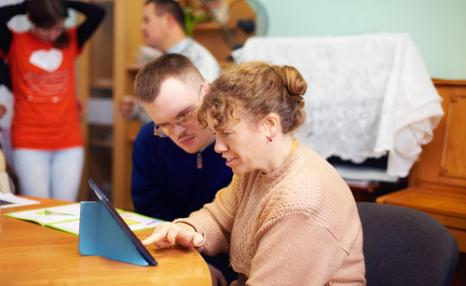 Social worker working with a class of people with learning difficulties