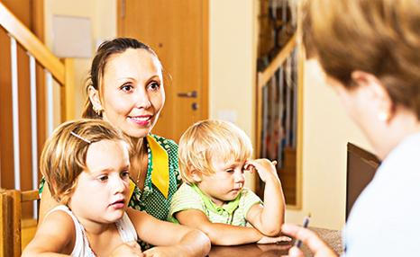 Social worker showing her laptop to woman with two children
