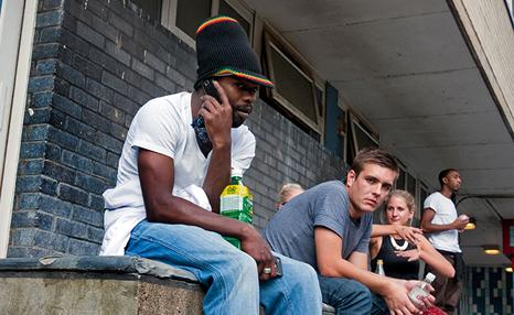A group of young adults sitting outside of a building